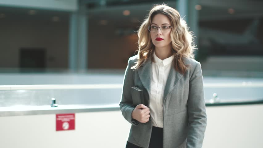 Confident business woman is walking along the modern business center. the manager is in a hurry to meet with clients or a business partner. woman in business suit holding notebook in hands