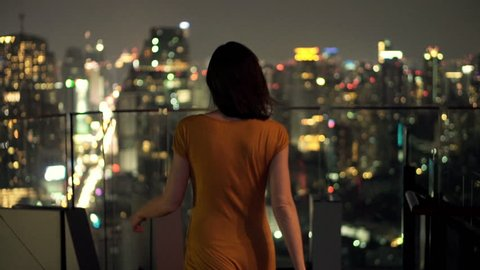 Young woman looking at cityscape at night