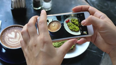 Female Hands Photographing Food For Breakfast By Smartphone. Coffee And Avocado Toast.