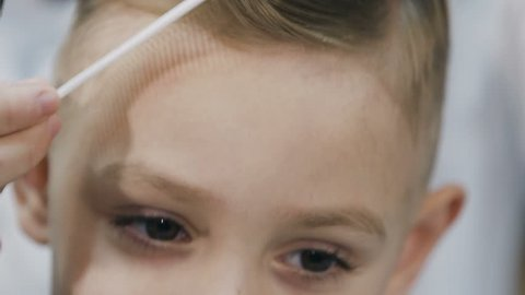 Close up of the boy's face in who a new stylish haircut. The barber makes a hairstyle for a little boy in a male barbershop. Barber makes haircute styling for the boy at barbershop, slow motion