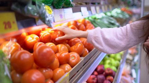 Woman's hands taking red tomatoes in supermarket. Close up, Woman's hand shopping buying   selection choosing tomatoes vegetable. Young girl, woman buying tomatoes vegetables. health, shopping bask
