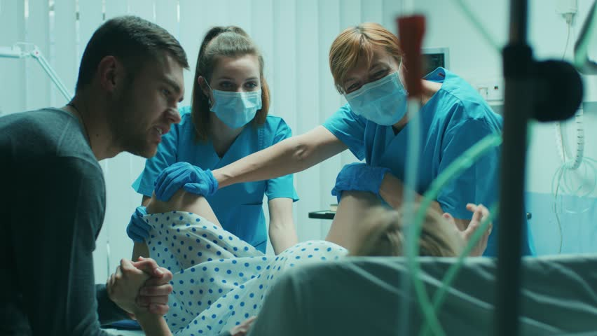 In the Hospital Woman in Labor Pushes to Give Birth, Obstetricians Assisting, Husband Holds Her Hand for Support. Modern Maternity Ward with Professional Midwives. Shot on RED EPIC-W 8K Helium Camera.