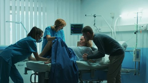 In the Hospital Woman in Labor Pushes to Give Birth, Obstetricians Assisting, Spouse Holds Her Hand. Modern Maternity Hospital Ward with Professional Midwives. Shot on RED EPIC-W 8K Helium Camera.