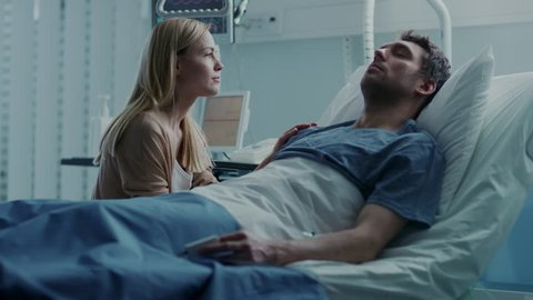 In the Hospital Sick Man Lying on the Bed, His Visiting Wife Hopefully Sits Beside Him and Prays for His Rapid Recovery. Tragic, Somber and Melancholy Scene. Shot on RED EPIC-W 8K Helium Cinema Camera