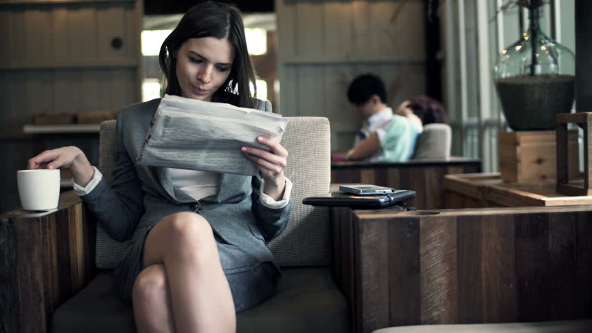 Young businesswoman reading newspaper and drinking coffee in cafe