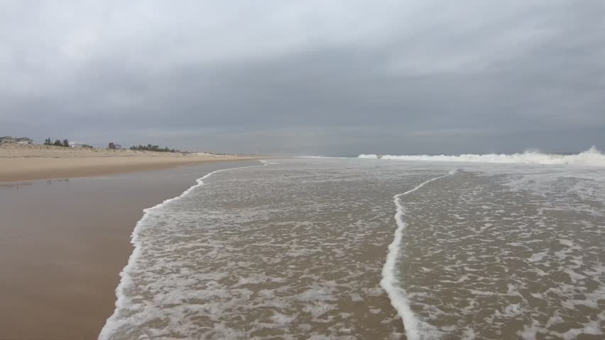 Still shot down the shoreline on an overcast, stormy, cloudy day on the coast of Delaware. The beach looks like the beaches in Maryland, New Jersey, Virginia, North and South Carolina, and Florida