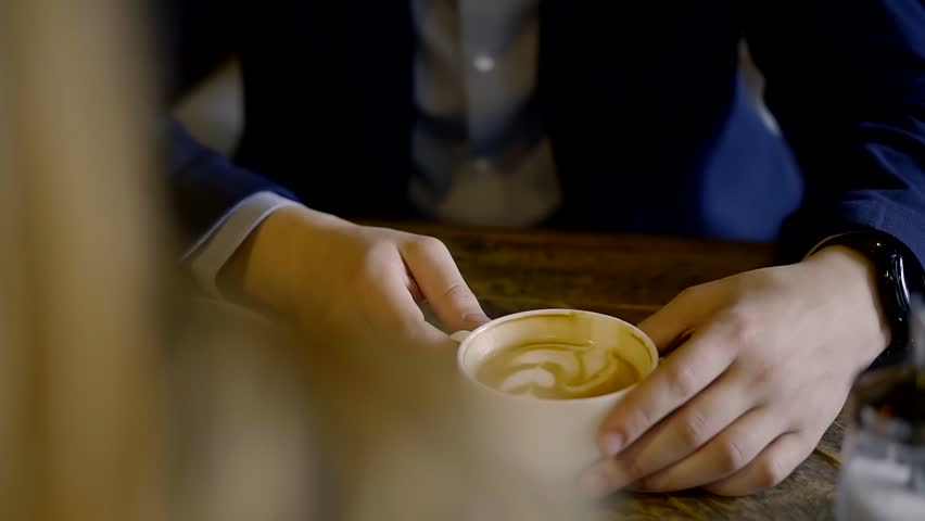 Young man is wearing dark blue suit is drinking coffee in restaurant, sitting at table with blonde | Shutterstock HD Video #1009328675