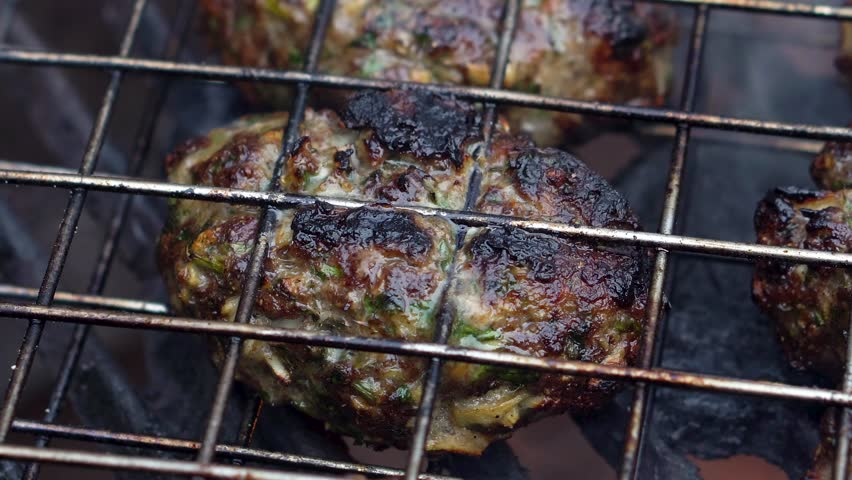 Extreme closeup of a single kofta cooking on a hot grill with smoke and flames. | Shutterstock HD Video #1009333625