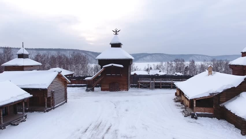 Aerial Museum Taltsy spire eagle Ethnographic Dramatic Open air wooden houses chirch Traditions Russia Siberia Roof in snow Baikalsky tract. Angara river mountains. Winter dark sky cloudy. Drone Close | Shutterstock HD Video #1009353005