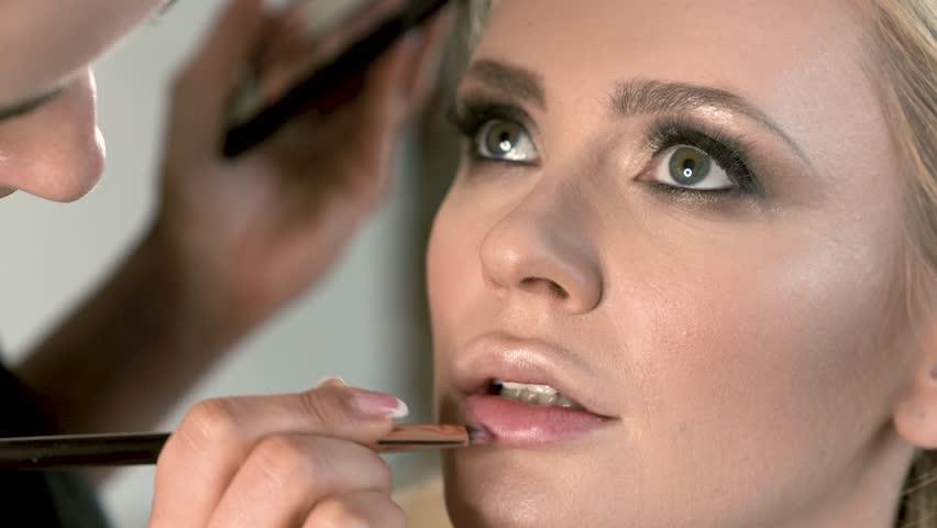 Professional make-up artist applying lip primer for liquid lipstick. Primer under lipstick. Close-up