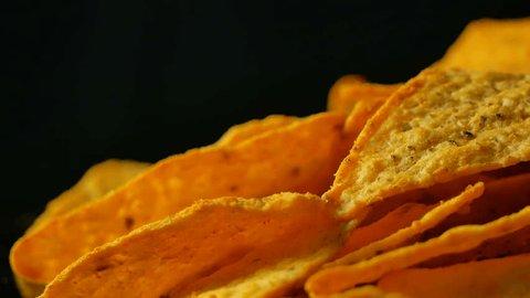 4K UHD footage of triangle nacho chips slowly rotating, close up
