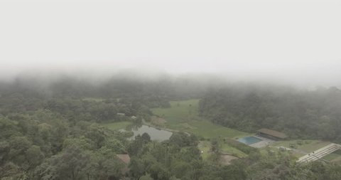 A slow motion aerial view of a landscape amidst mist and passing clouds.