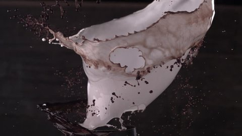 A slow motion clip of milk and coffee gushing out together in a circular motion.