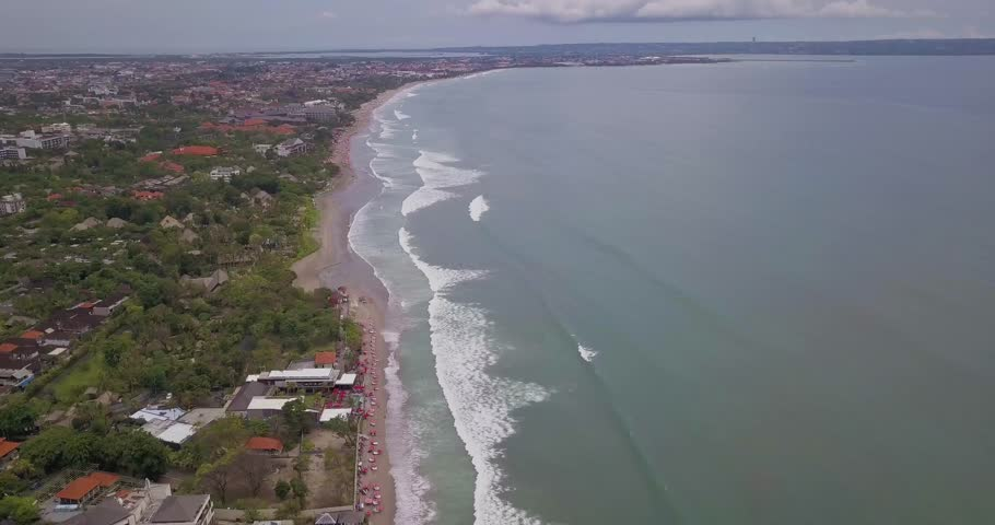 Drone shot 4k of a beach in Seminyak Bali as the big waves meet the sand shore with a nice landscape view of the beach background of Kuta.