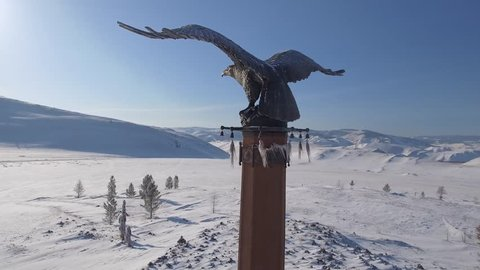 Approach bronze Monument Stella Eagle Shaman Buryatia Mystical ritual unique Spaced wings High mountains open space landscape. Winter snow frost cold blue sky day. Russia Baikal. Aerial Drone Close-up