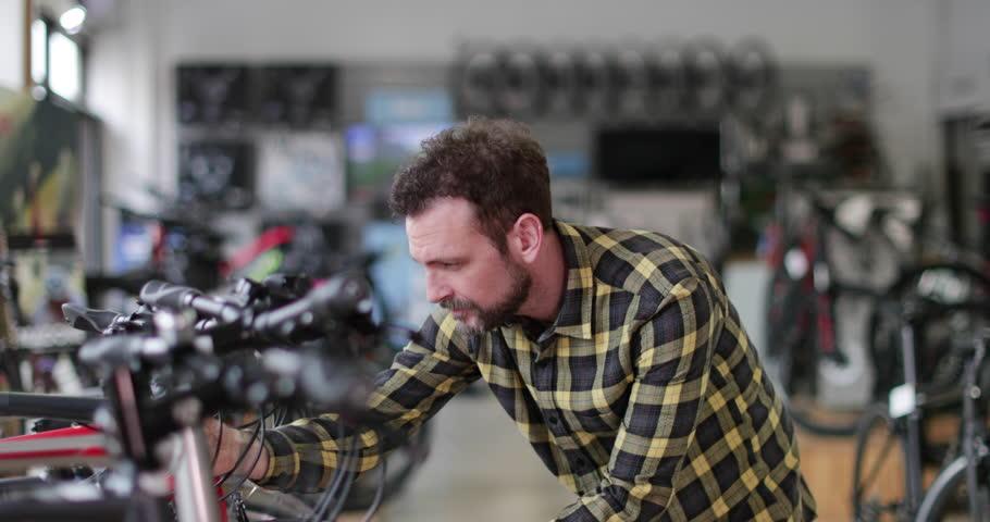 Adult male choosing a bike in a cycle store   Shutterstock HD Video #1009422605