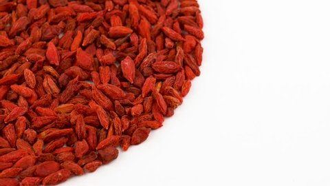 Half frame circle shaped heap of organic dried goji berries rotating on turn table. Isolated on white. Loopable. Close up macro. View from above/overhead.