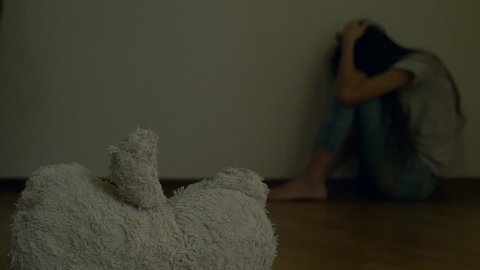 a desperate child in depression sits at the wall of his room, tries to attempt suicide. next to it is an abandoned soft toy. 4k, slow motion.