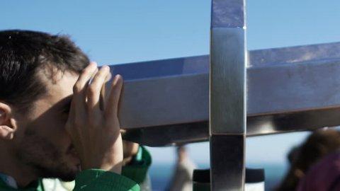 Male tourist looking at cityscape through binoculars at sightseeing platform