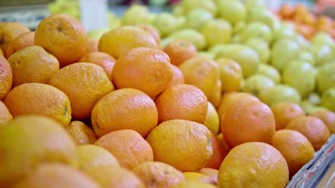 Dynamic close up of oranges and lemons on a local farmers market with moving camera in warm colors in soft-focus in the background