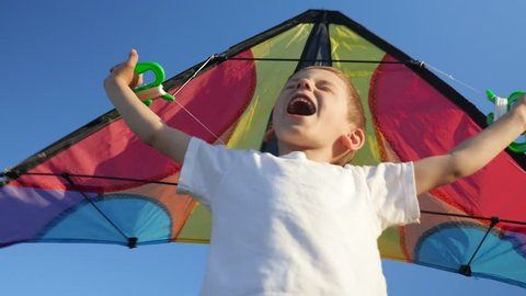 joyful kid boy playing with bright toy kite against summer blue sky background. Childhood. Fantasy, imagination concept.