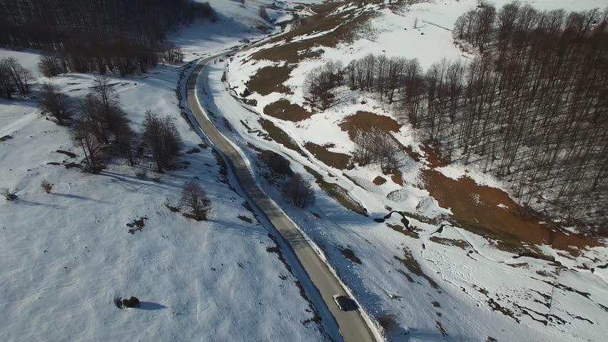 AERIAL: White SUV jeep car driving along the winding mountain pass road through the forest. People traveling, road trip on curvy road through beautiful countryside scenery in sunny winter