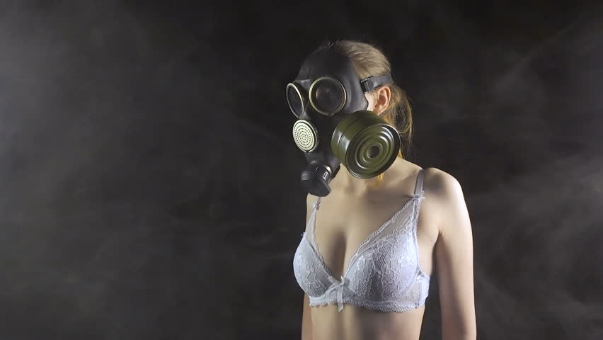 Young girl in gas mask wearing white bra