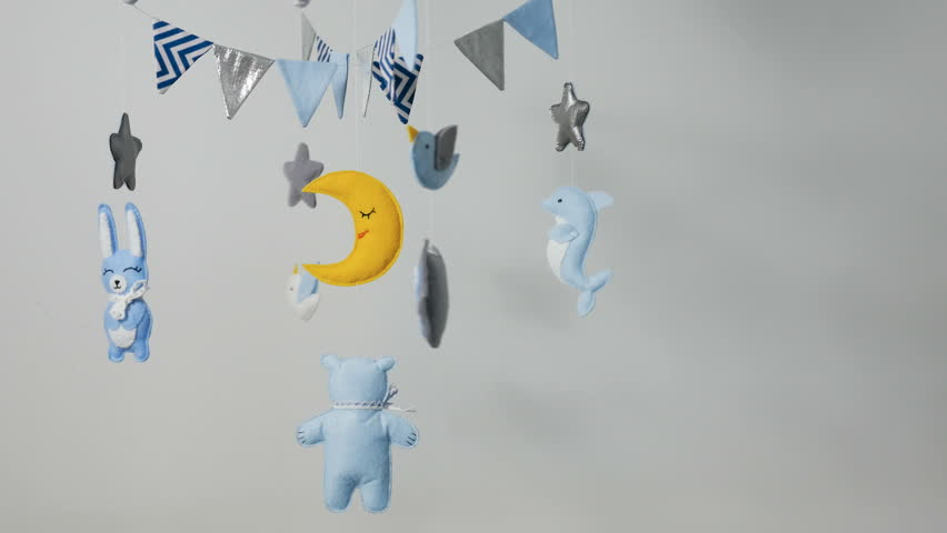 Baby mobile with blue hand-stitched animal and bird toys with yellow moon on white wall background | Shutterstock HD Video #1009516925