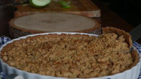 Apple crisp or Apple crumble pie a dessert baked chopped apples topped with a crisp streusel crust. set on wooden table.