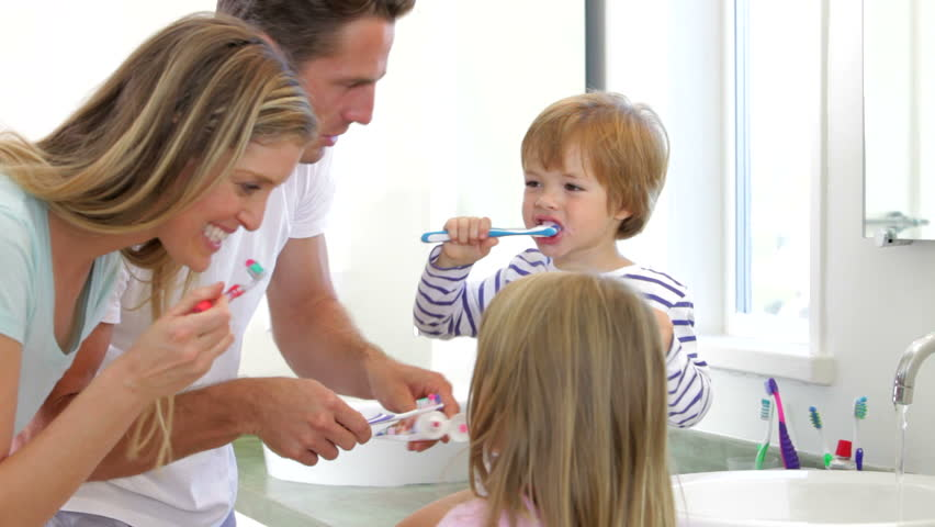 Family gathered in bathroom wearing pajamas and brushing teeth. Shot on Canon 5d Mk2 with a frame rate of 30fps