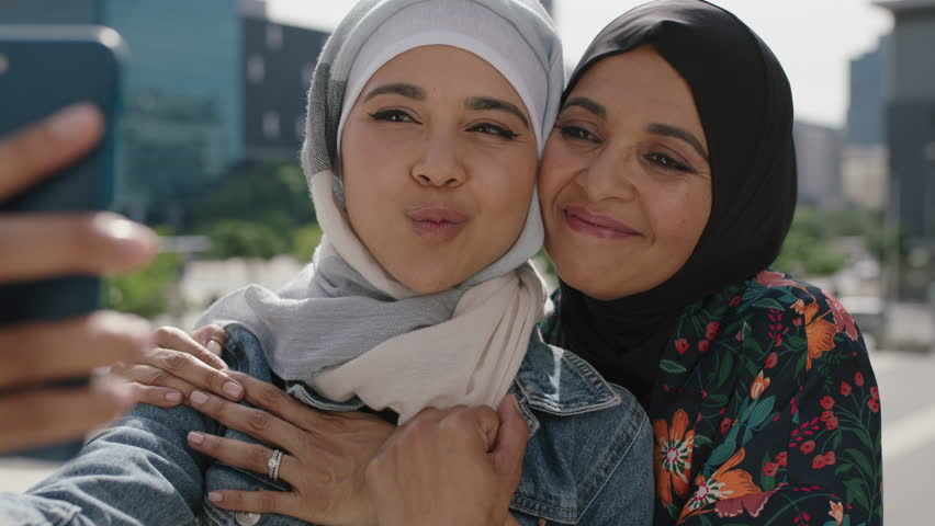 Close up portrait of muslim mother and daughter smiling cheerful embrace posing taking selfie photo using smartphone in sunny urban city wearing hijab headscarf | Shutterstock HD Video #1009534085