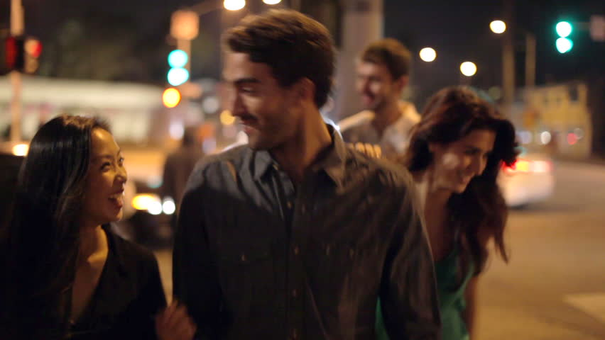 Group of friends on night out walk along street towards camera.Shot on Sony FS700 in PAL format at a frame rate of 25fps #10095365