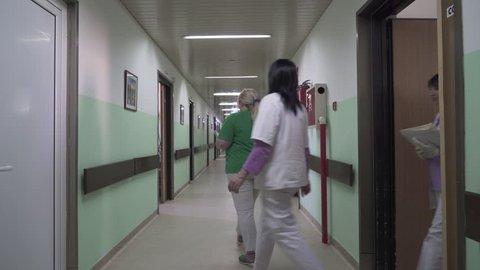 Nurses team holding in hands medical documentation and walking through the hall of hospital department and coming in room, concept medicine, steady cam, tracking, gimbal, overhead shot, interior scene
