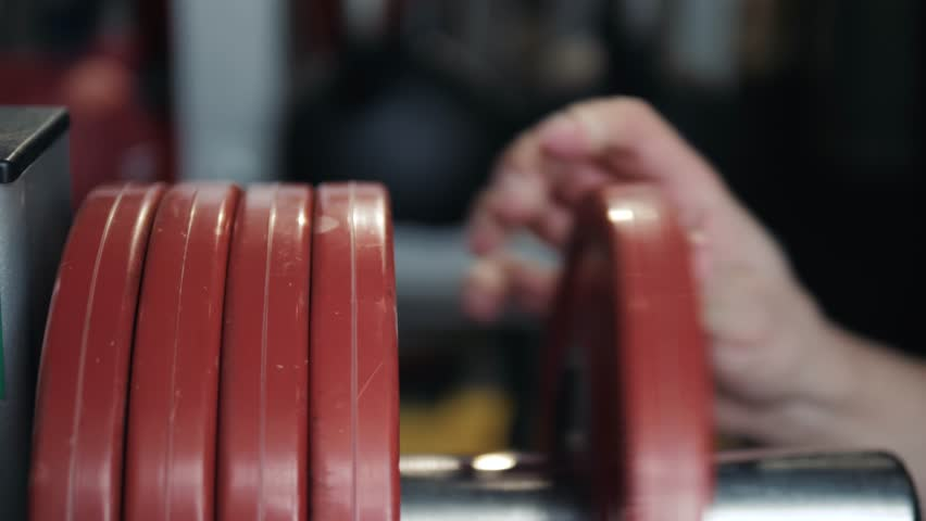 Closeup macro close up of handsome bodybuilder guy prepare to do exercises with barbell in a gym, keep barbell plate in hands, sport man | Shutterstock HD Video #1009542635