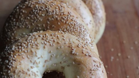Pick 3 fresh bagels from a pile of freshly baked bagels. HD video.