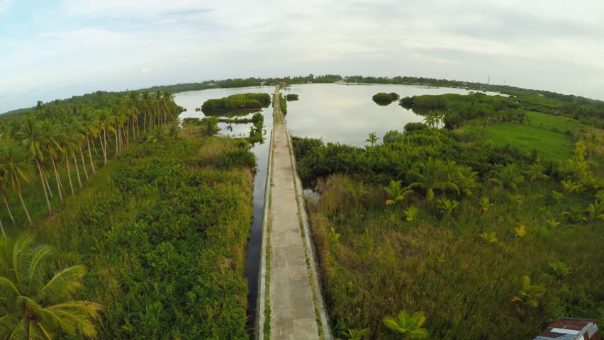 Filipino village with a lake. Anda. Bohol Island. Evening time. Aerial view. Fine artificial road.