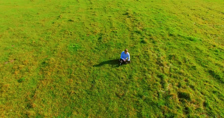 UHD 4k aerial view. Low orbital flight over businessman sitting on green grass with notebook (pad) at yellow rural wheat field. Radial movement. | Shutterstock HD Video #1009558385