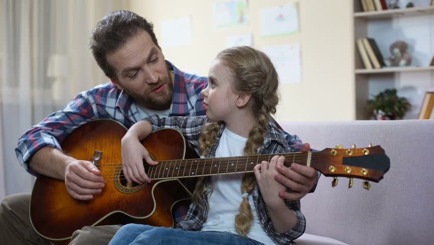 Father teaching daughter to play guitar at home, musical hobby, family leisure #1009578635