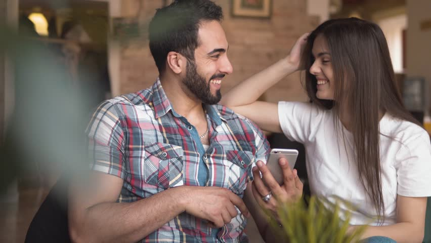 Happy young couple looking at photos on smartphone, good-looking bearded man and pretty long-haired woman enjoying sweet memories with newest technology, indoor shot in european cafe during lunchbreak | Shutterstock HD Video #1009589765