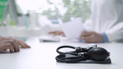 Professional female doctor meeting a patient in the office, she is giving him a prescription for hypertension, sphygmomanometer on the foreground