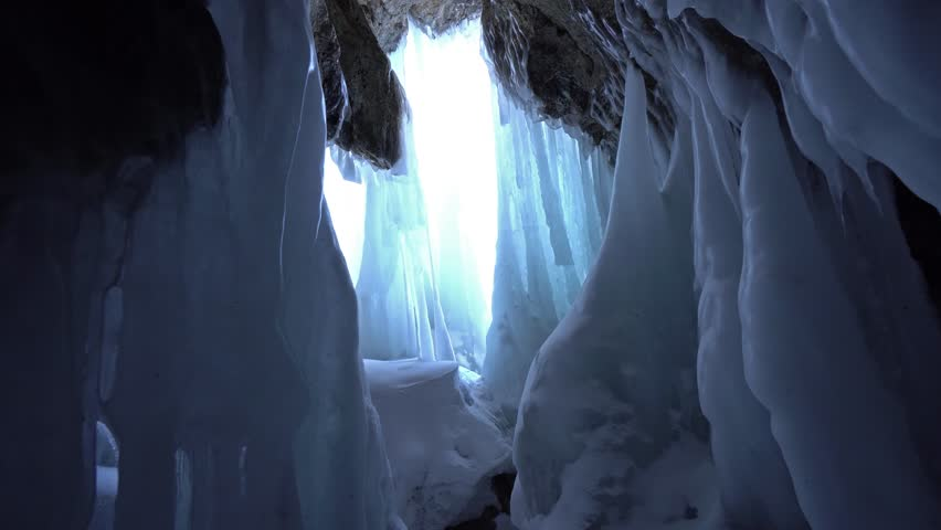 Dolly Gimbal inside Cave blue ice white sharp Close splashes turquoise shiny pillars long sunshine bright light. Innocent wild abstract untouched mysterious texture. Winter cold. Russia Baikal Arctic