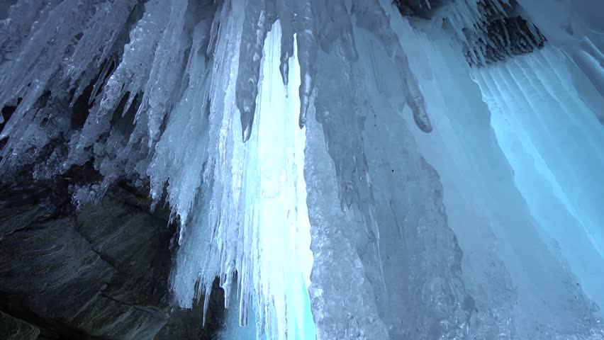 Dolly Close Aaround shiny transparent sharp blue ice hanging lump texture ceiling cave rock inside unique view up. Mystic impress. Winter frost innocent ecology. Russia Baikal Arctic Gimbal