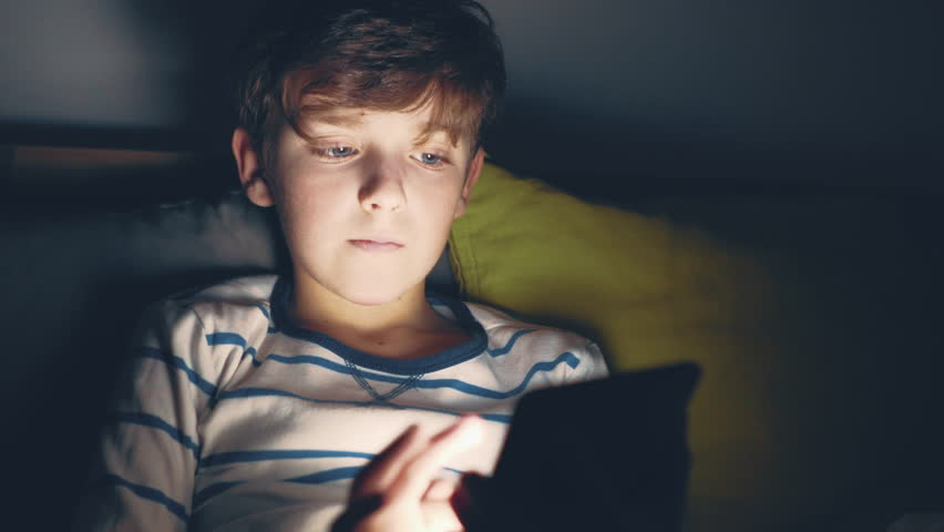 A happy smiling boy in pajamas lies in bed on cushions and enthusiastically plays on a smartphone in a game in the dark. The face of the child is lit by a bright monitor