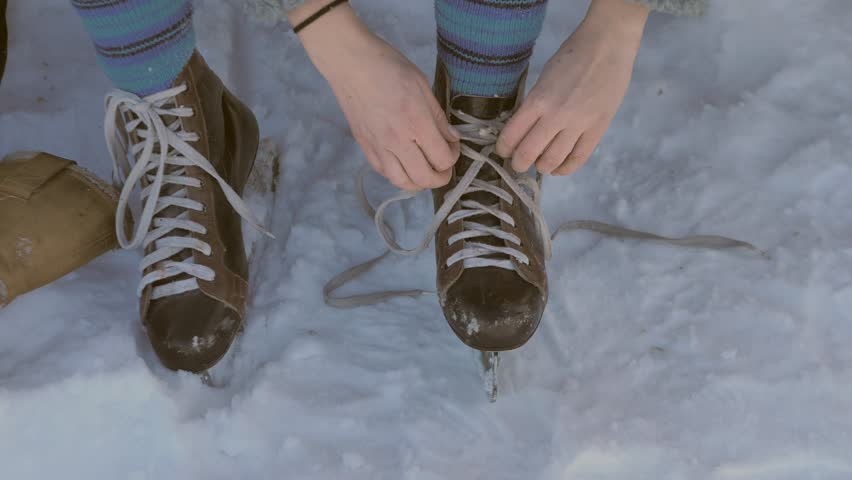 Young person is getting ready for ice skating - fixing or tying laces for retro looking leather ice skates | Shutterstock HD Video #1009644005