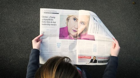 PARIS; FRANCE - SEP 24; 2017: View from above of woman reading latest newspaper Le Monde with portrait of Hillary Clinton article about how Donald Trump has lost the moral leadership of United States