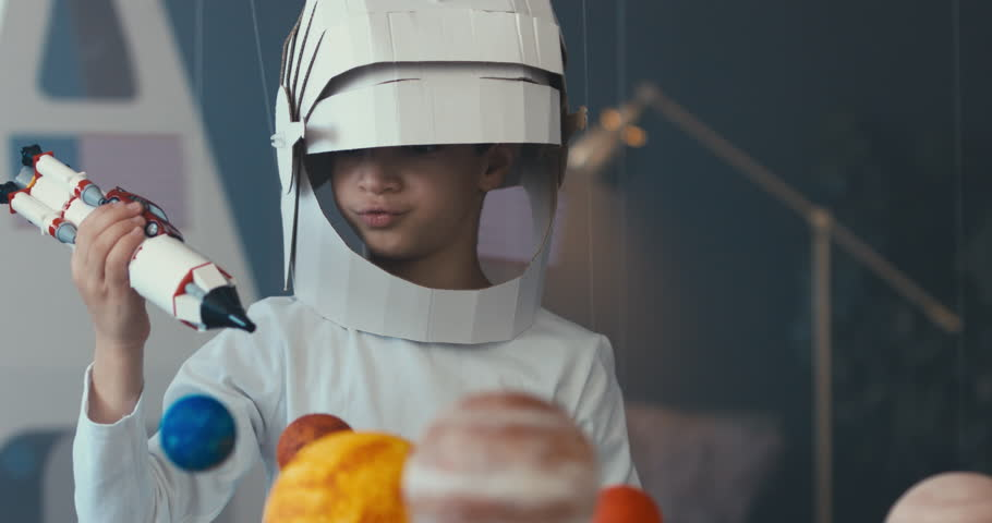 CU Cute little boy wearing cardboard astronaut helmet flying toy rocket through planets, exploring deep space. 4K UHD 60 FPS SLOW MO | Shutterstock HD Video #1009647965