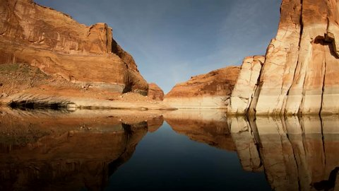 A beautiful clip of a perfect red sandstone reflection on Lake Powell. The water is calm and still with cliffs rising straight from the water. An amazing destination for fishermen and water sports.