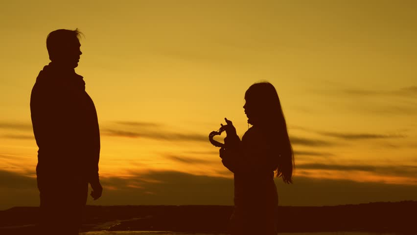 Little child gives in heart to his dad at sunset. Love of father and daughter. Sunset. | Shutterstock HD Video #1009660655