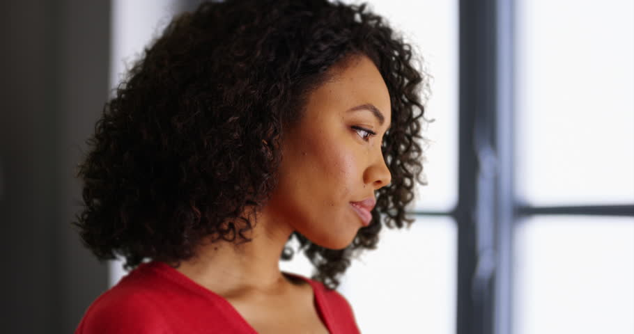 Young black lady deep in thought turning to face camera in indoor setting. Casual African-American millennial girl turning towards camera inside building. 4k