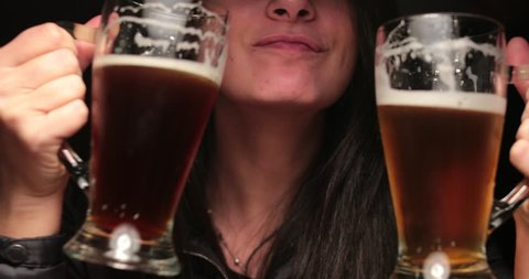 Woman drinking beer from two large mugs. silly woman celebrating with draft beers toasting herself. Funny girl drinks beer acting silly in 4K